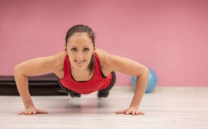 100354855 - portrait of a young woman with braces doing pushups in a gym.